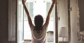 窓を開けて光を浴びる女性