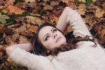 落ち葉の上に横たえる女性