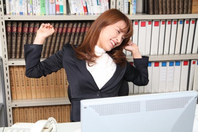 デスクワーク終わりに背伸びをする女性