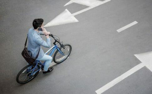 自転車に乗って電話をする男性